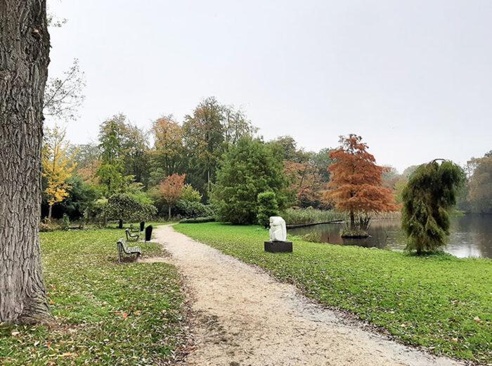 Caminho ao longo do lago no Amstelpark, com bancos, obras de arte e muitas árvores.